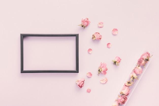 テーブルの上のバラの花びらを持つ空白のフレーム 無料写真