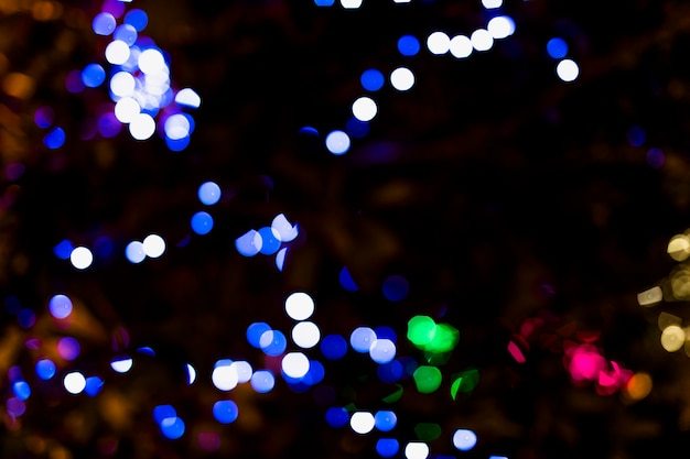 闇の背景を持つ照らされたカラードット 無料写真
