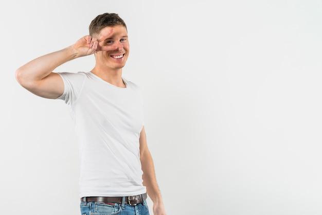 白い背景の上の彼の片目の前で平和のジェスチャーを作る若い男 無料写真