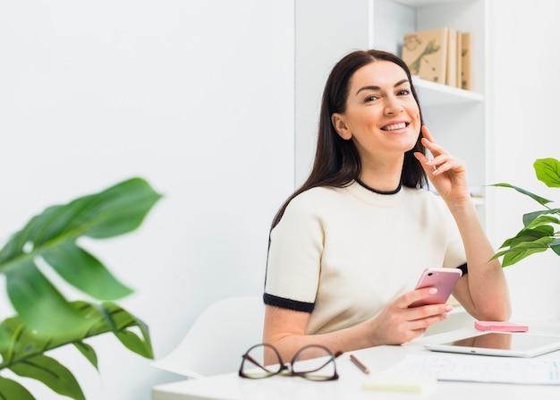 スマートフォンでオフィスのテーブルに座っている女性 無料写真