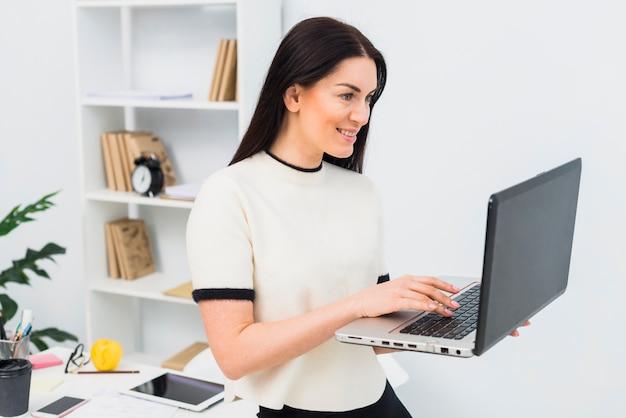 女性のオフィスでラップトップを使用して 無料写真