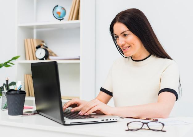 テーブルでノートパソコンのキーボードで入力する女性 無料写真