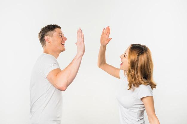 白い背景で隔離のお互いにハイタッチを与える若いカップルの笑顔 無料写真