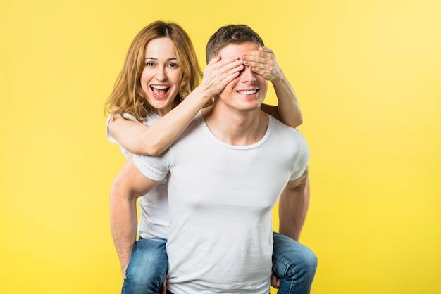 黄色の背景に対して彼氏の背中に乗っている間目を覆っている幸せな若い女 無料写真