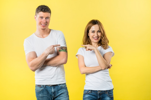 Улыбающиеся молодые пары, указывая пальцем друг к другу, глядя в камеру Бесплатные Фотографии
