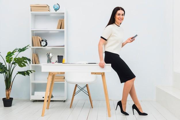 スマートフォンでオフィスに立っている若い女性 無料写真
