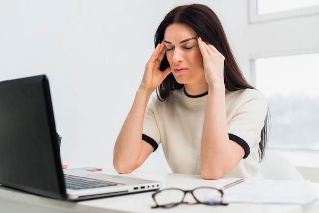 Подчеркнул женщина сидит за столом с ноутбуком Бесплатные Фотографии
