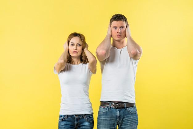 黄色の背景に彼らの耳を覆う若いカップルの肖像画 無料写真