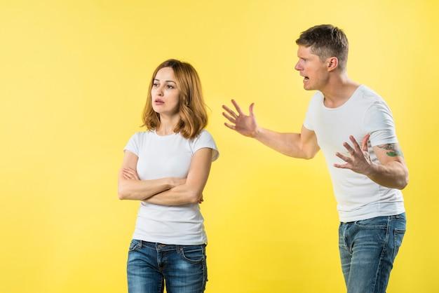 Молодой человек кричит на злой блондинке, стоя на желтом фоне Бесплатные Фотографии