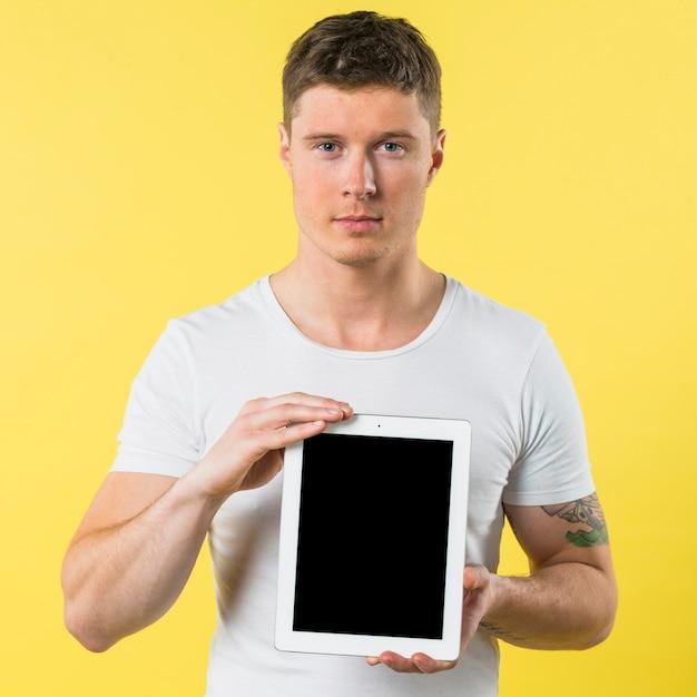 Портрет молодого человека показывая пустой экран цифровую таблетку против желтого фона Бесплатные Фотографии