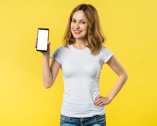 Счастливая молодая женщина с руки на ее бедра, показывая мобильный телефон с белым экраном Бесплатные Фотографии