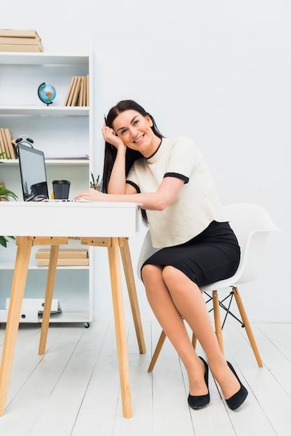 ノートパソコンをテーブルに座って幸せな女 無料写真