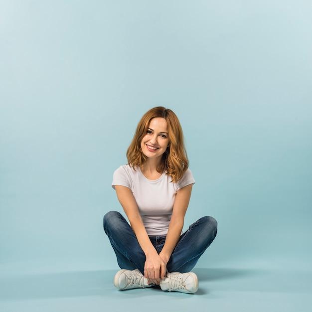 青い背景の床に座っている笑顔の若い女性の肖像画 無料写真