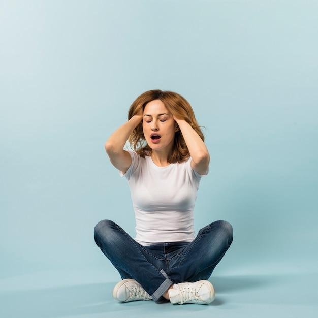 Ленивая молодая женщина с двумя руками в волосы на синем фоне Бесплатные Фотографии
