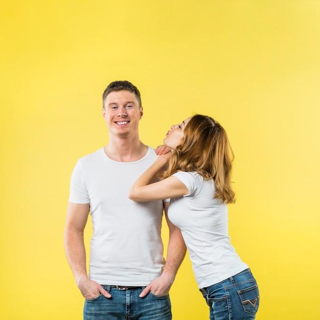 Молодая женщина, опираясь на плечо своего парня дует поцелуй на желтом фоне Бесплатные Фотографии