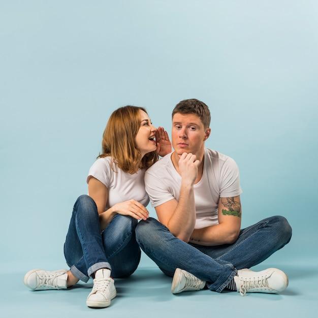 青い背景に彼のボーイフレンドに秘密を告げる若い女性の肖像画 無料写真