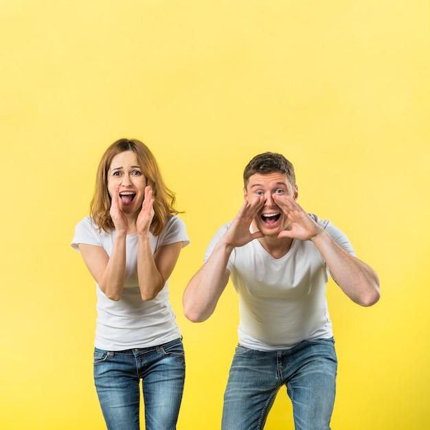 Молодая пара громко кричать на желтом фоне Бесплатные Фотографии