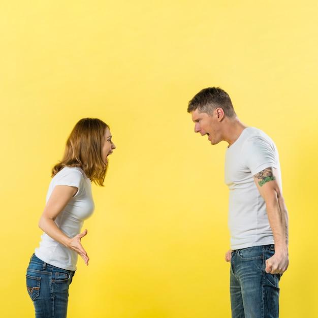 黄色の背景に対してお互いに叱る若いカップルの側面図 無料写真