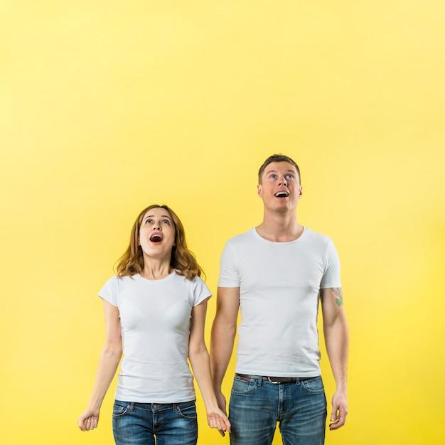 黄色の背景に対して見上げて幸せな若いカップル 無料写真