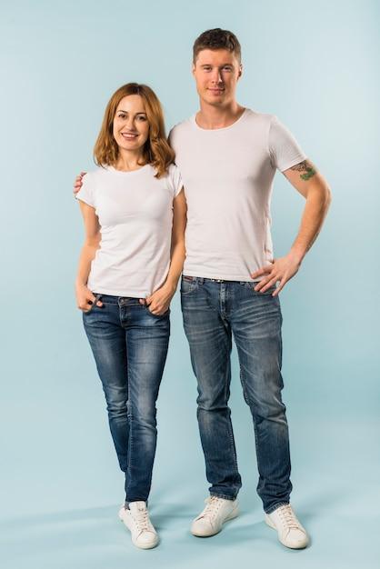 青い背景に対して立っている若いカップルの肖像画 無料写真