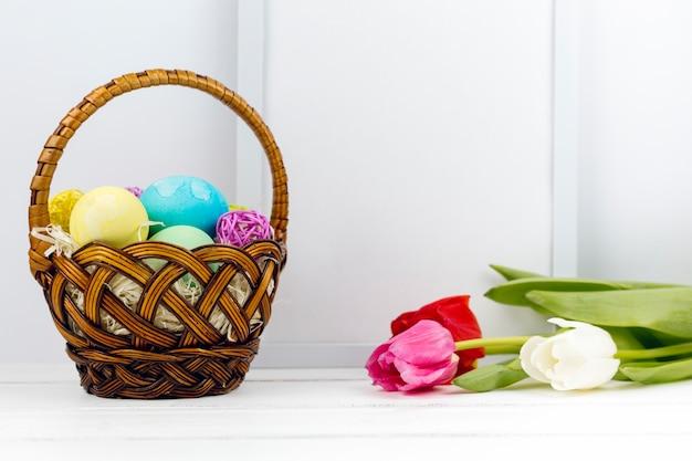 Пасхальные яйца в корзине с тюльпанами и пустой кадр на столе Бесплатные Фотографии