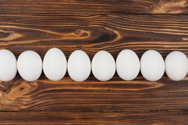 木製のテーブルの上の白い鶏の卵の行 無料写真