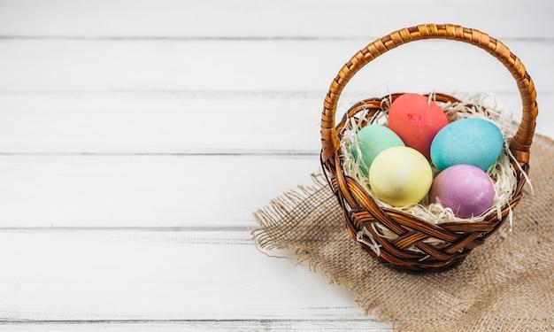Пасхальные яйца в корзине на деревянный стол Бесплатные Фотографии