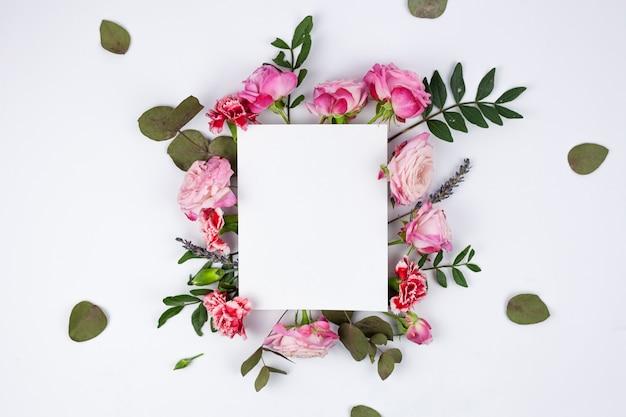 白い背景の上の美しい花に白い空白の紙 無料写真