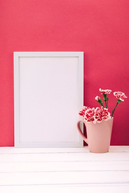 白い木製のテーブルの上に空のフォトフレームとカーネーションの花瓶 無料写真