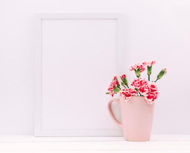 テーブルの上に空のフォトフレームと花瓶にカーネーションの花 無料写真