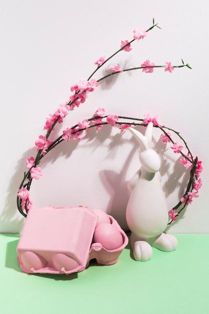 ウサギの置物と花のラックのイースターエッグ 無料写真
