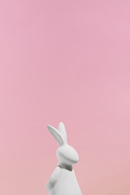 ピンクの背景に白ウサギの置物 無料写真
