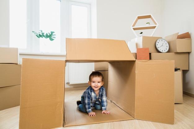 自宅で開いている段ボール箱の中の笑顔の赤ちゃん幼児 無料写真