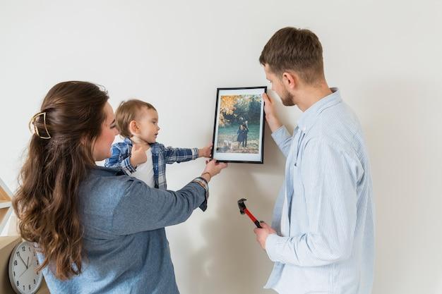 新しい家で壁に額縁を持って幸せな家族のクローズアップ 無料写真