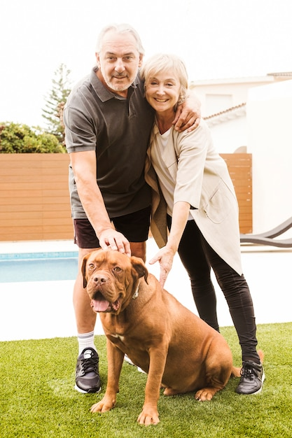 庭で犬と年配のカップル 無料写真