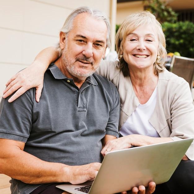 年配のカップルが庭でラップトップを使用して 無料写真