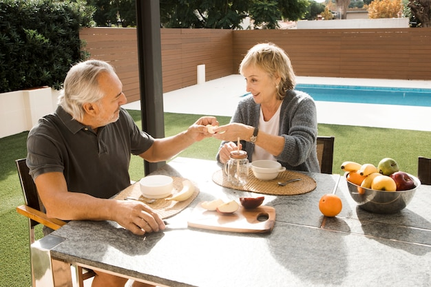 年配のカップルが庭で朝食をとって 無料写真