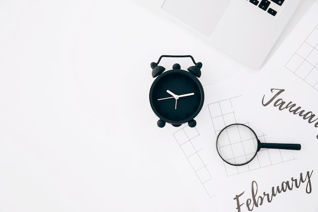 黒の目覚まし時計。ノートパソコンと白い背景に対して紙の上の虫眼鏡 無料写真
