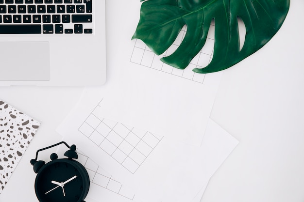 方眼紙。目覚まし時計;モンスターの葉と白い机の上のノートパソコン 無料写真