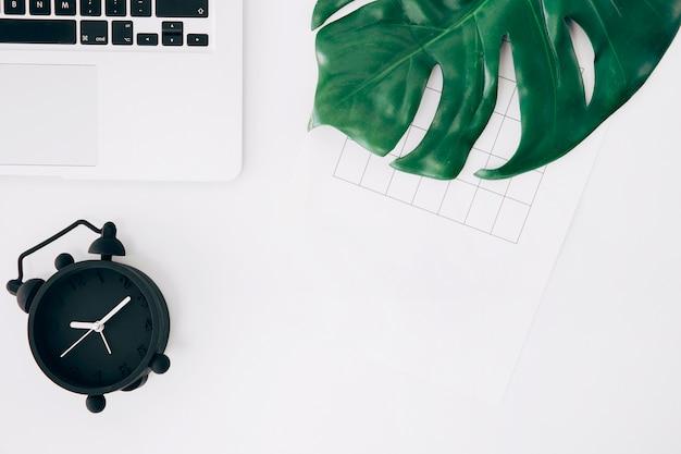黒い目覚まし時計の上から見た図。ノートパソコン白い机の上のページと緑のモンスターの葉 無料写真