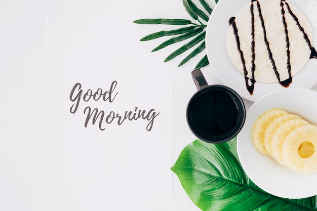 パイナップルスライストルティーヤとコーヒー白い背景の上の紙の上のおはよう本文と葉の上 無料写真