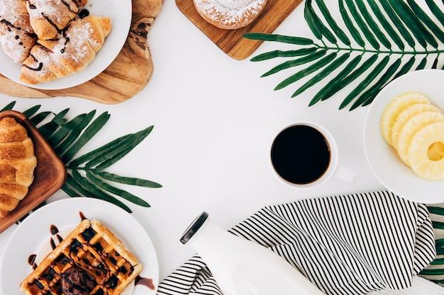 Вид сверху ломтиков ананаса; запеченный круассан; вафель; булочек; лепешек; бутылка молока и кофе на белом фоне Бесплатные Фотографии