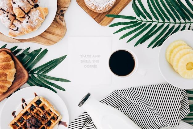 焼きたての朝食に囲まれたメモ帳のメッセージ。白い机の上のコーヒーとパイナップルのスライス 無料写真