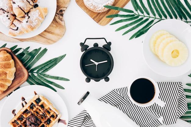 クロワッサンに囲まれた黒い目覚まし時計。ワッフル;バン;コーヒー;白い机の上のボトルとパイナップルのスライス 無料写真