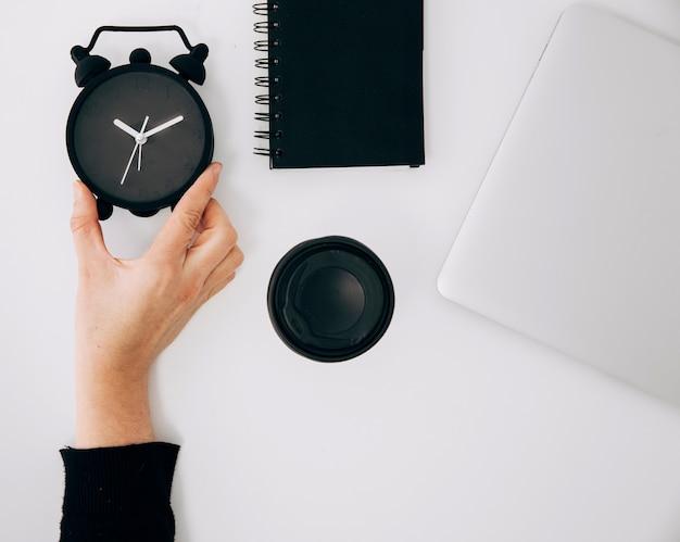 黒い目覚まし時計を持っている人の手のクローズアップ。スパイラルメモ帳。白い机の上のノートパソコンとテイクアウトのコーヒーカップ 無料写真