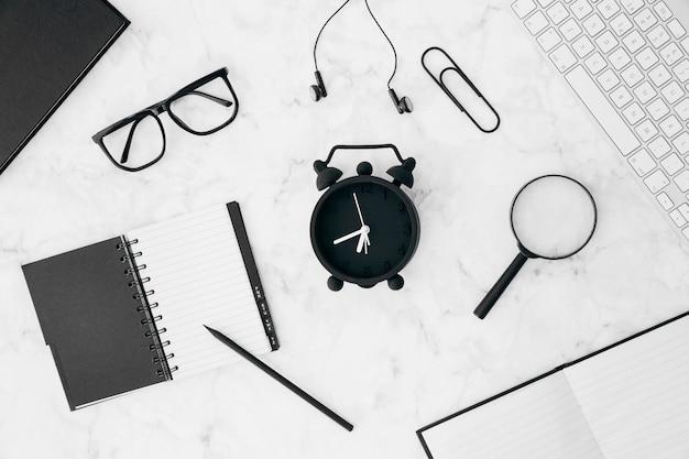 鉛筆;日記;めがねイヤホンペーパークリップ;虫眼鏡。キーボードと白い机の上の日記と目覚まし時計 無料写真