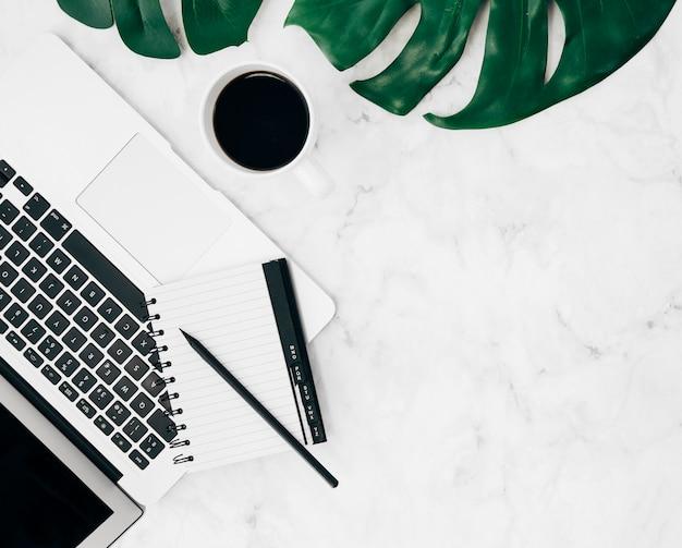 ラップトップ上の日記と鉛筆の俯瞰。コーヒーカップと大理石の背景にモンステラの葉 無料写真