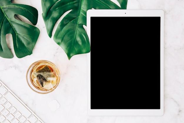 グラスにティーバッグを入れた熱い飲み物を醸造する。モンステラの葉。キーボードとデジタルタブレットの白い机の上 無料写真