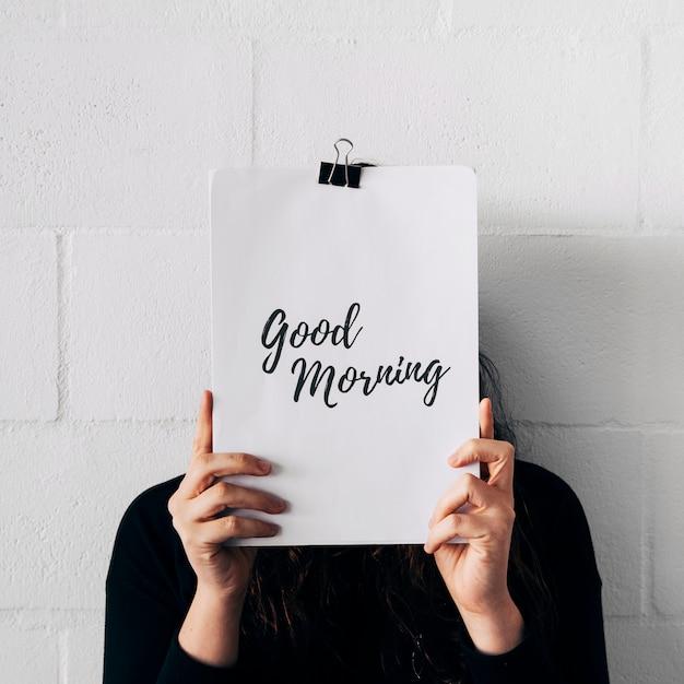 紙を保持している女性のクローズアップは彼女の顔の前にクリップとおはようテキストを添付します。 無料写真