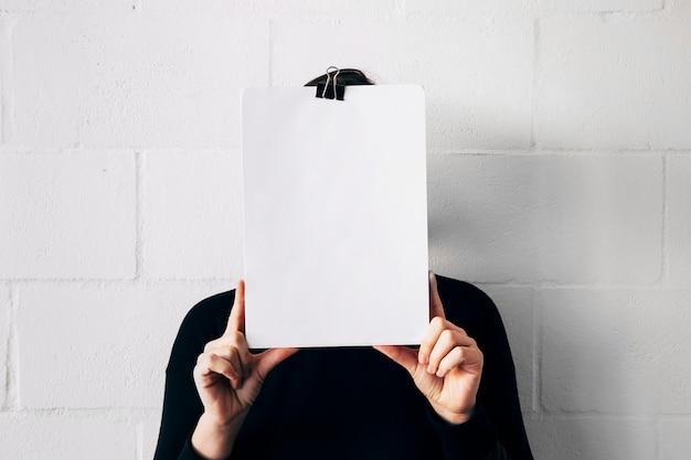 白い壁に対して彼女の顔の前でホワイトペーパーを保持している女性 無料写真